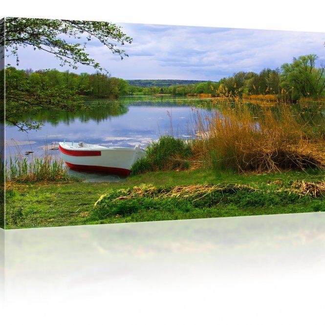 Ruderboot angeschwemmt auf einem See Bild auf Leinwand